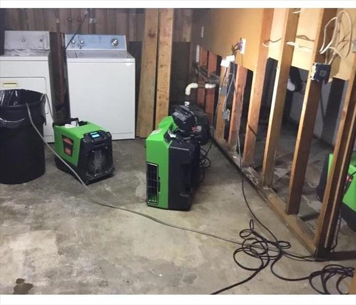 SERVPRO green drying machines placed in a basement