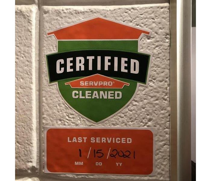 A painted white cement wall with the Certified: SERVPRO Cleaned shield and date serviced sticker displayed.