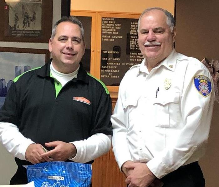 A SERVPRO employee smiling for a photo with the fire department chief