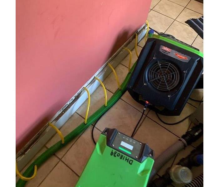 A photo of SERVPRO drying equipment placed next to a red wall