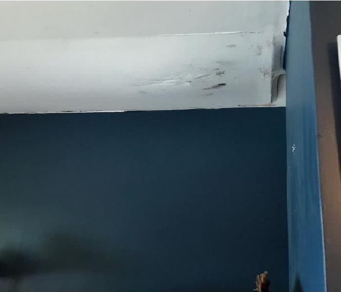 A white sheet rock ceiling bulging and breaking from water damage