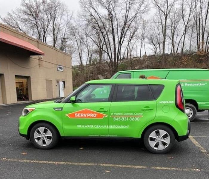 2 green SERVPRO vehicles parked in front of a commercial business