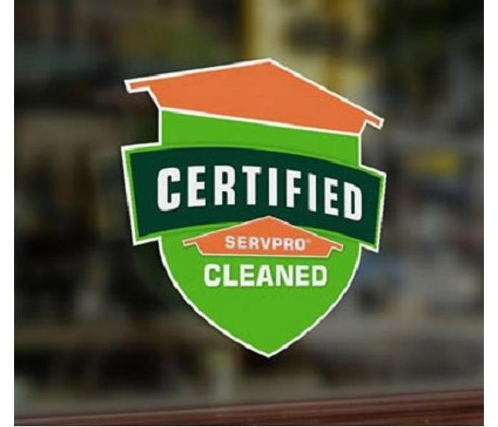 "An image of a badge colored in orange and green stating "" Certified: SERVPRO Cleaned"""