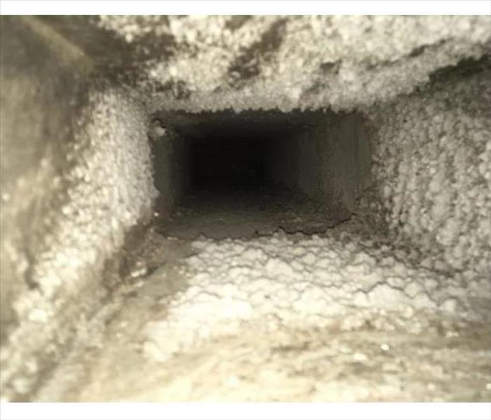 A photo of an interior air duct covered with dust and debris
