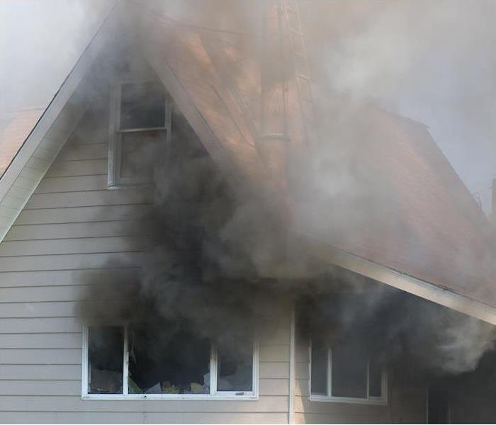 Black smoke coming out of broken windows in a burning house