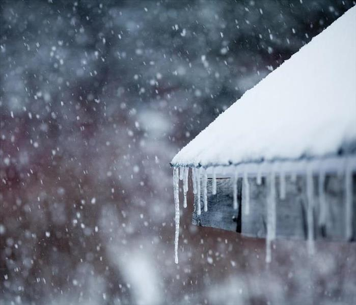 A view of snow falling and accumulating over a home's roof