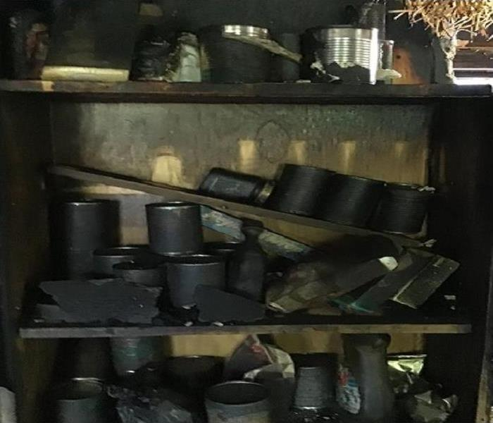 Cans of food covered completely in black soot from a house fire.